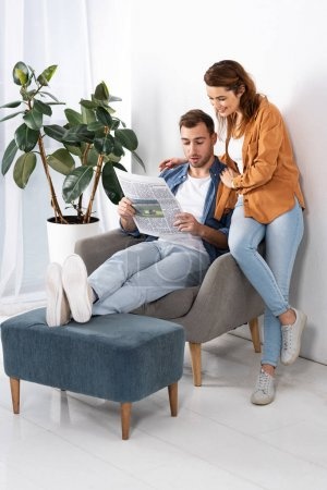 happy woman standing and hugging handsome man with newspaper at home