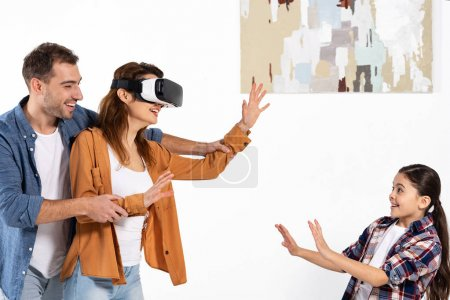 Photo for Happy man holding hands of cheerful woman in virtual reality headset near daughter - Royalty Free Image