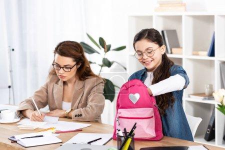 Photo pour Enfant gai regardant sac à dos près de la mère dans des lunettes de travail dans le bureau - image libre de droit