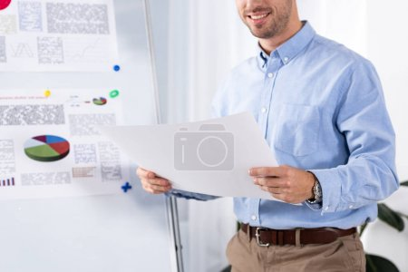 Photo for Cropped view of cheerful businessman holding blank paper in office - Royalty Free Image
