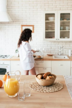 Photo for Selective focus of woman preparing breakfast with orange juice and croissants on foreground - Royalty Free Image