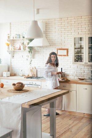 Photo pour Jolie femme dans la chemise blanche regardant loin tout en préparant le petit déjeuner dans la cuisine - image libre de droit