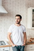 """Постер, картина, фотообои """"smiling man in jeans standing with hands in pockets and looking away in kitchen"""""""
