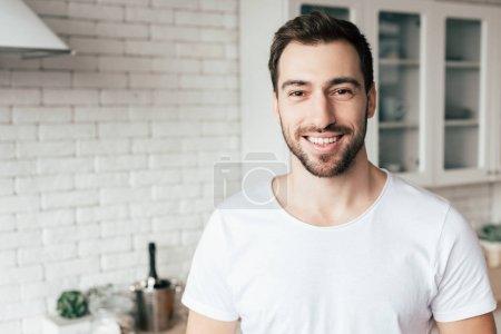 Photo pour Vue de face de l'homme barbu souriant regardant la caméra - image libre de droit