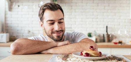 plan panoramique d'homme barbu souriant regardant des crêpes dans la cuisine