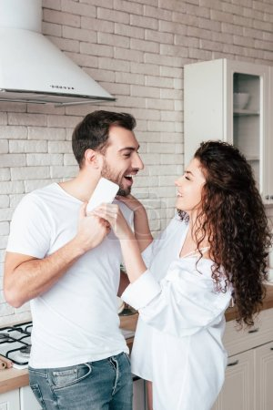 Photo for Laughing couple looking at each other in kitchen - Royalty Free Image
