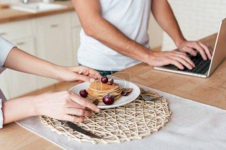 Photo pour Vue partielle du couple avec de savoureuses crêpes et ordinateur portable - image libre de droit