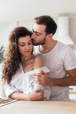 bearded man embracing and kissing girlfriend in kitchen