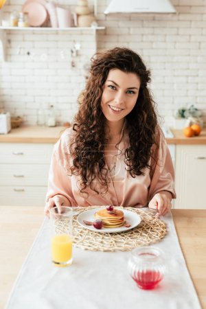 Photo for Smiling curly young woman sitting at table with plate of pancakes - Royalty Free Image