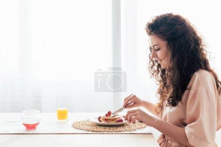 Photo pour Vue latérale de sourire fille manger des crêpes dans la cuisine - image libre de droit