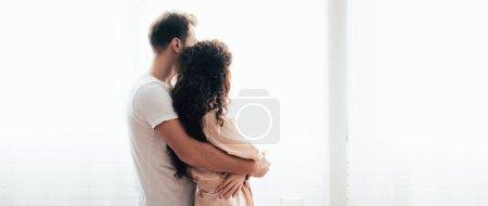 Photo pour Tir panoramique de l'homme embrassant petite amie et regardant loin - image libre de droit
