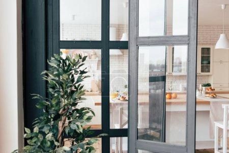 Photo pour Fenêtres de cuisine ouvertes, table servie avec nourriture et plante verte - image libre de droit
