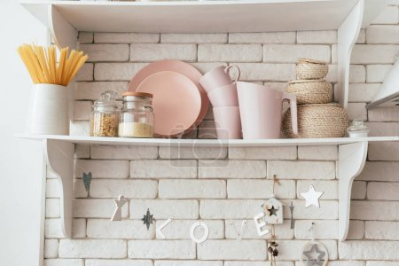 Photo for Shelf with plates, cups, jars and pasta in kitchen - Royalty Free Image
