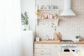 modern light kitchen with tableware, cooking utensils and decoration