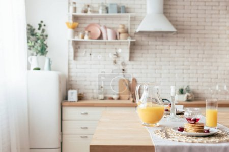 Photo for Served table with pancakes and orange juice in kitchen - Royalty Free Image