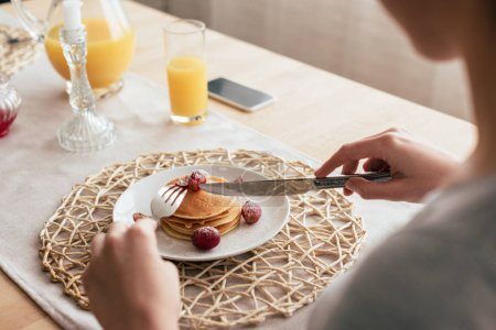 Photo for Partial view of woman eating pancakes in kitchen - Royalty Free Image
