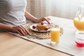 partial view of woman sitting at table with pancakes in kitchen