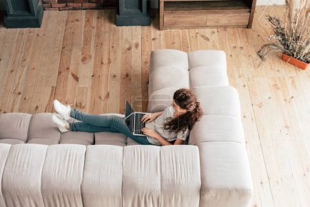 overhead view of woman sitting on sofa and using laptop