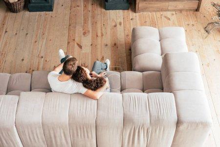 Foto de Overhead view of couple embracing on sofa in living room - Imagen libre de derechos