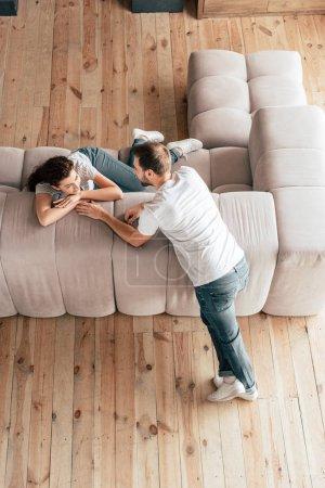 Blick von oben auf ein glückliches Paar, das sich im Wohnzimmer anschaut