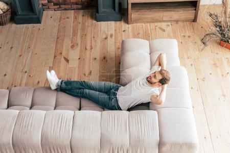 Photo pour Vue aérienne de l'homme souriant détendu couché sur le canapé - image libre de droit