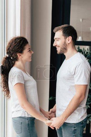 Photo pour Couple souriant tenant la main et se regardant - image libre de droit
