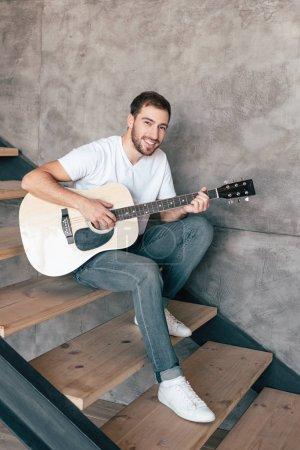 Photo pour Homme barbu de sourire s'asseyant sur des escaliers et jouant la guitare acoustique - image libre de droit