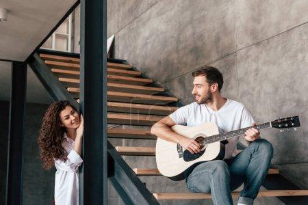 Photo pour Homme barbu de sourire s'asseyant sur des escaliers et jouant la guitare acoustique à la petite amie - image libre de droit