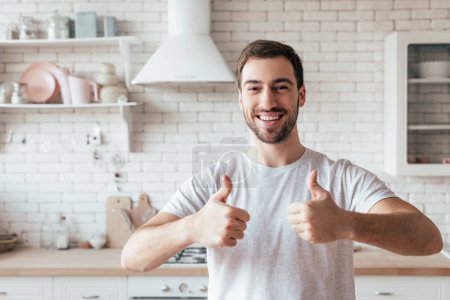 Photo for Front view of laughing bearded man showing thumbs up in kitchen - Royalty Free Image