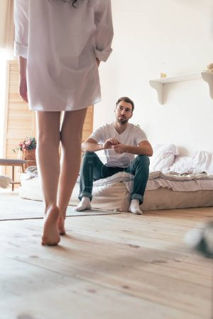 Photo pour Partial view of sexy woman in shirt and bearded man sitting on bed in bedroom - image libre de droit