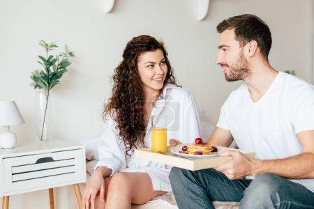Photo pour Couples de sourire avec le plateau avec le petit déjeuner regardant l'un l'autre dans la chambre à coucher - image libre de droit