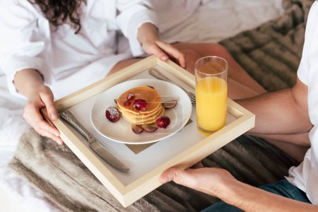 Photo for Partial view of couple holding tray with pancakes and glass of orange juice - Royalty Free Image