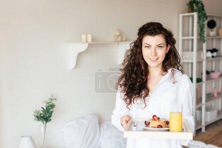 Photo pour Vue de face de jolie femme tenant plateau avec petit déjeuner dans la chambre - image libre de droit