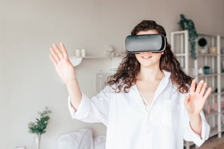 Photo for Smiling girl in vr headset waving hands in bedroom - Royalty Free Image