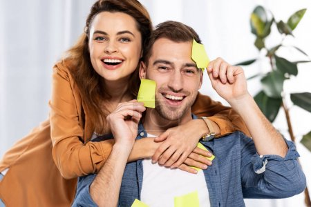 Photo for Cheerful woman hugging handsome man with yellow sticky notes - Royalty Free Image