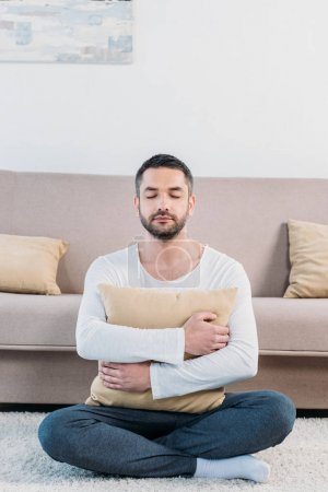 Photo for Handsome man with eyes closed sitting on carpet and hugging pillow at home in living room - Royalty Free Image