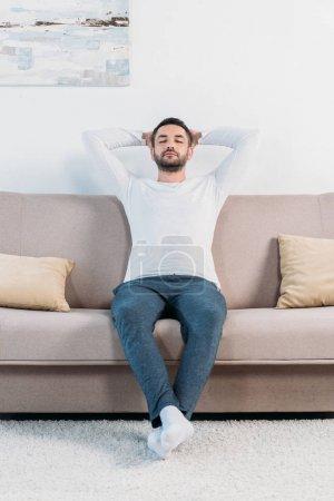 Photo pour Bel homme barbu avec les yeux fermés et les mains derrière le dos reposant sur le canapé à la maison - image libre de droit