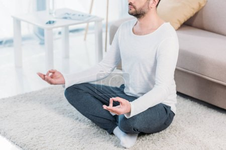 cropped view of man sitting on carpet in Lotus Pose and meditating at home