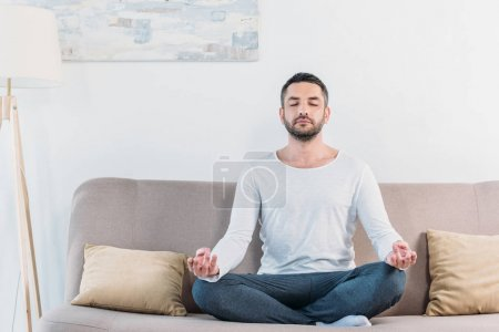Photo for Handsome man with eyes closed sitting on couch in Lotus Pose and meditating at home - Royalty Free Image