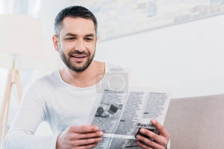 Photo pour Beau sourire homme barbu lisant le journal à la maison - image libre de droit