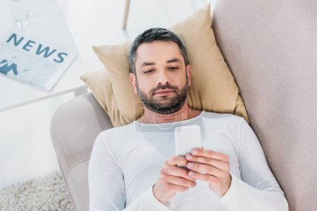Photo for Handsome man lying on couch and using smartphone at home - Royalty Free Image
