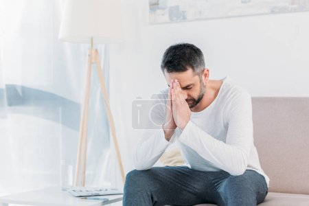 Photo for Handsome bearded man with eyes closed doing please gesture and praying at home - Royalty Free Image