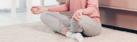Photo for Panoramic shot of woman in Lotus Pose practicing meditation at home in Living Room - Royalty Free Image