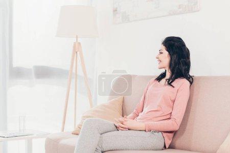 Photo pour Belle femme souriante assise sur le canapé avec les mains pliées à la maison - image libre de droit