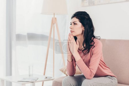 Photo for Beautiful woman sitting on couch, doing please gesture and praying at home - Royalty Free Image