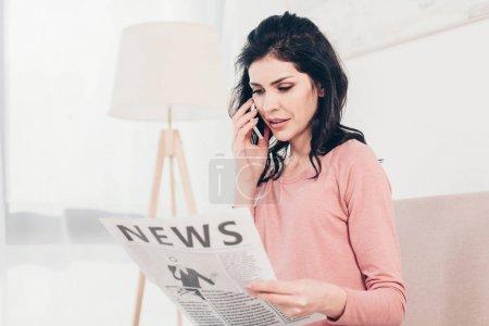 Photo pour Belle femme parler sur smartphone et lire le journal à la maison dans le salon - image libre de droit