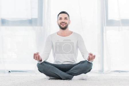 Photo for Happy handsome man sitting on carpet in Lotus Pose and meditating at home - Royalty Free Image