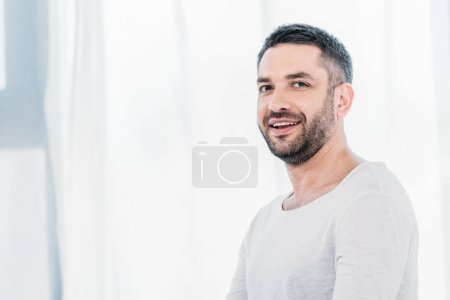 handsome bearded man looking at camera and smiling at home with sunlight and copy space