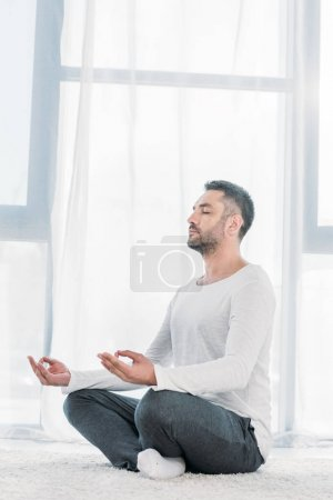 Photo pour Handsome man with eyes closed sitting on carpet in Lotus Pose and meditating at home - image libre de droit