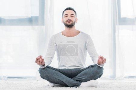 Photo pour Homme beau avec les yeux fermés s'asseyant sur le tapis dans la pose de Lotus et méditant à la maison - image libre de droit